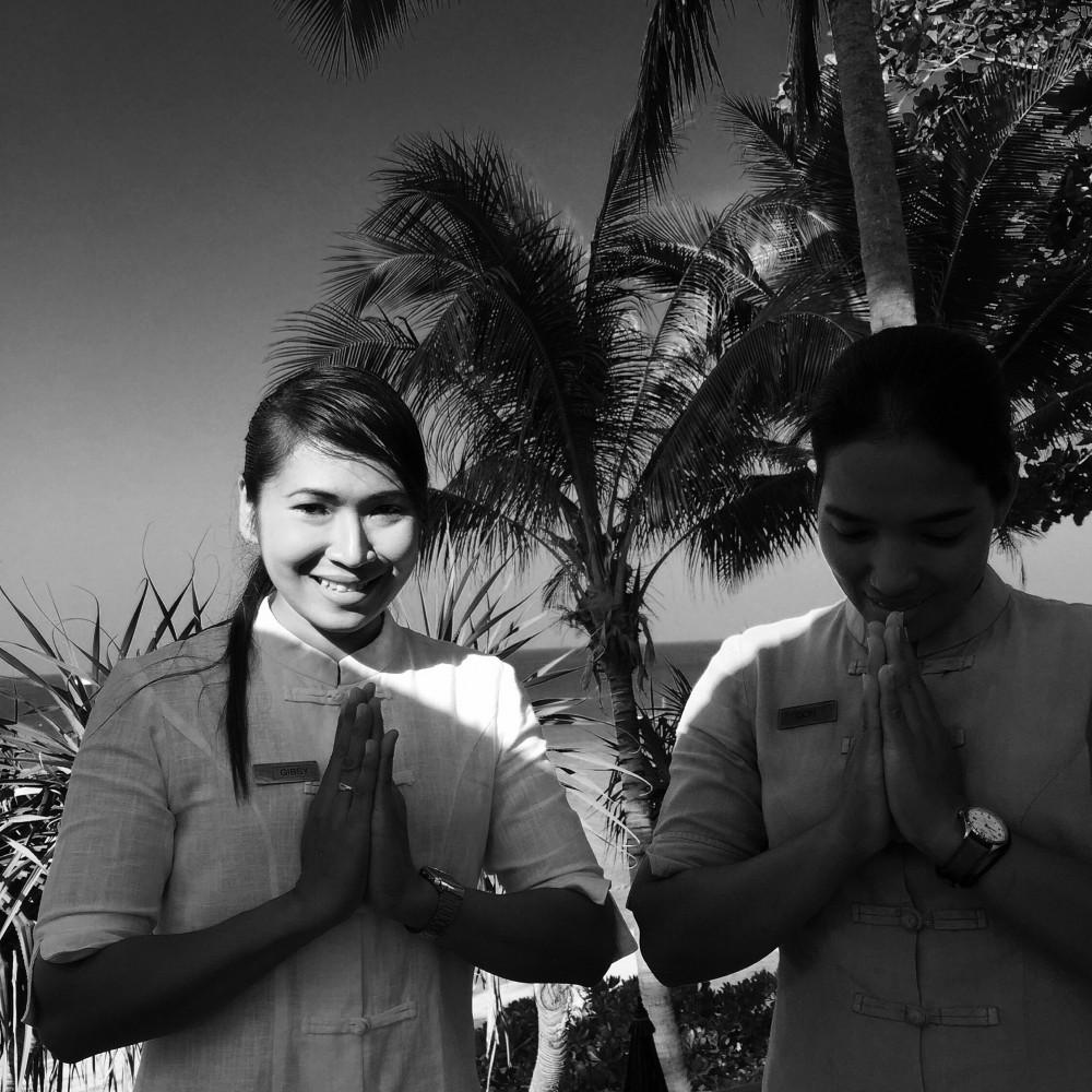 Thai staff with wai greeting at trisara resort phuket
